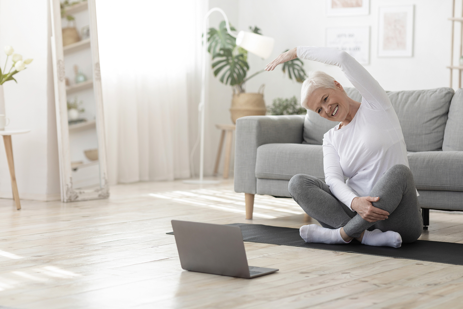 Senior woman enjoys following along with easy exercises to do at home