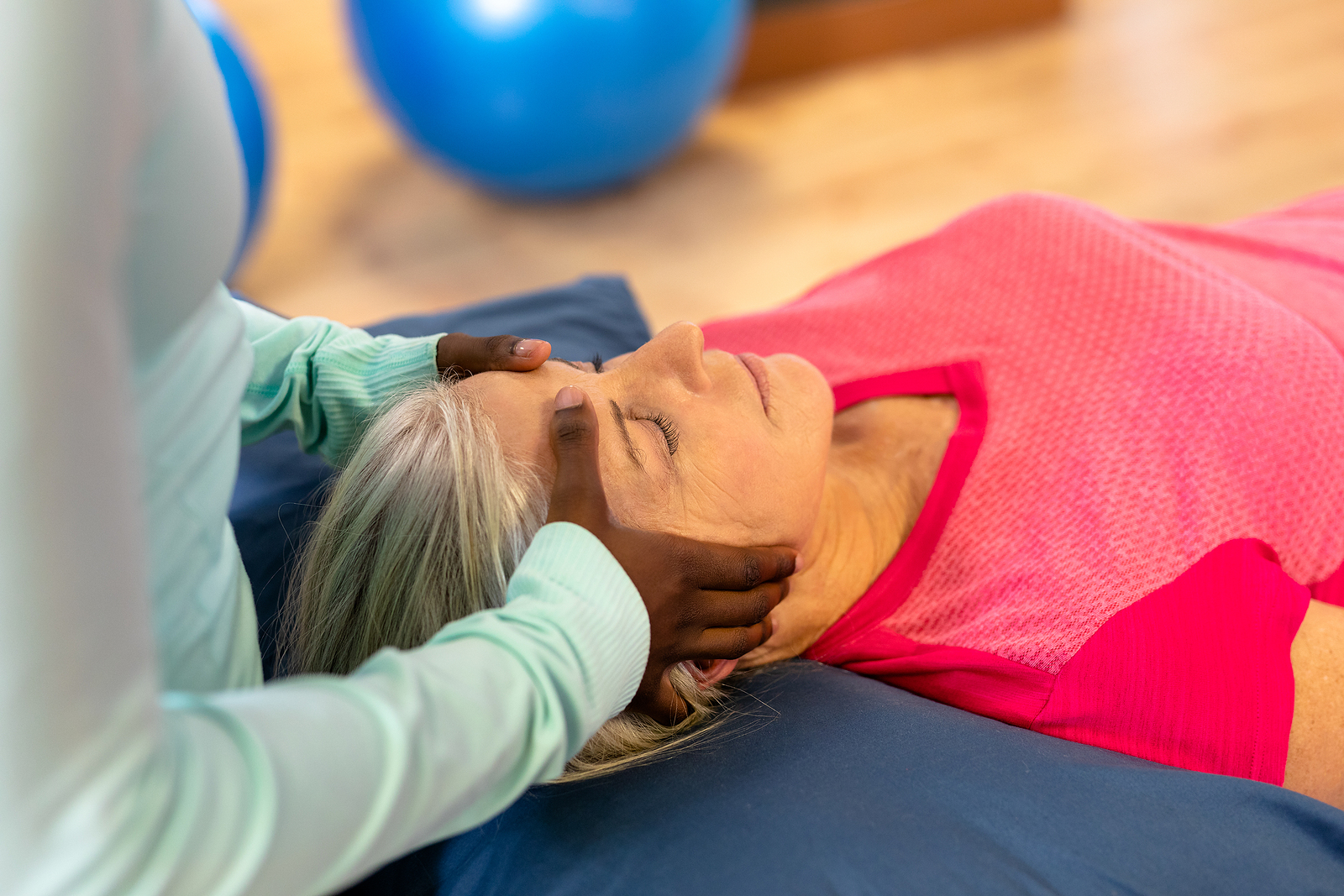 Woman relaxes as she receives massage therapy for seniors