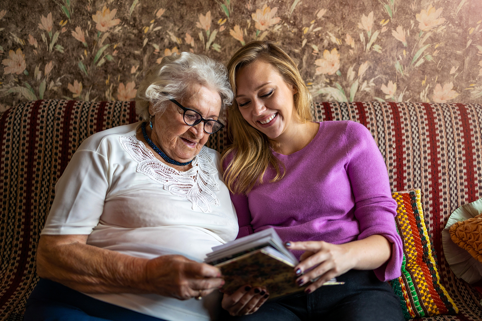 Senior woman and caregiver look at family photos to help combat normal forgetfulness