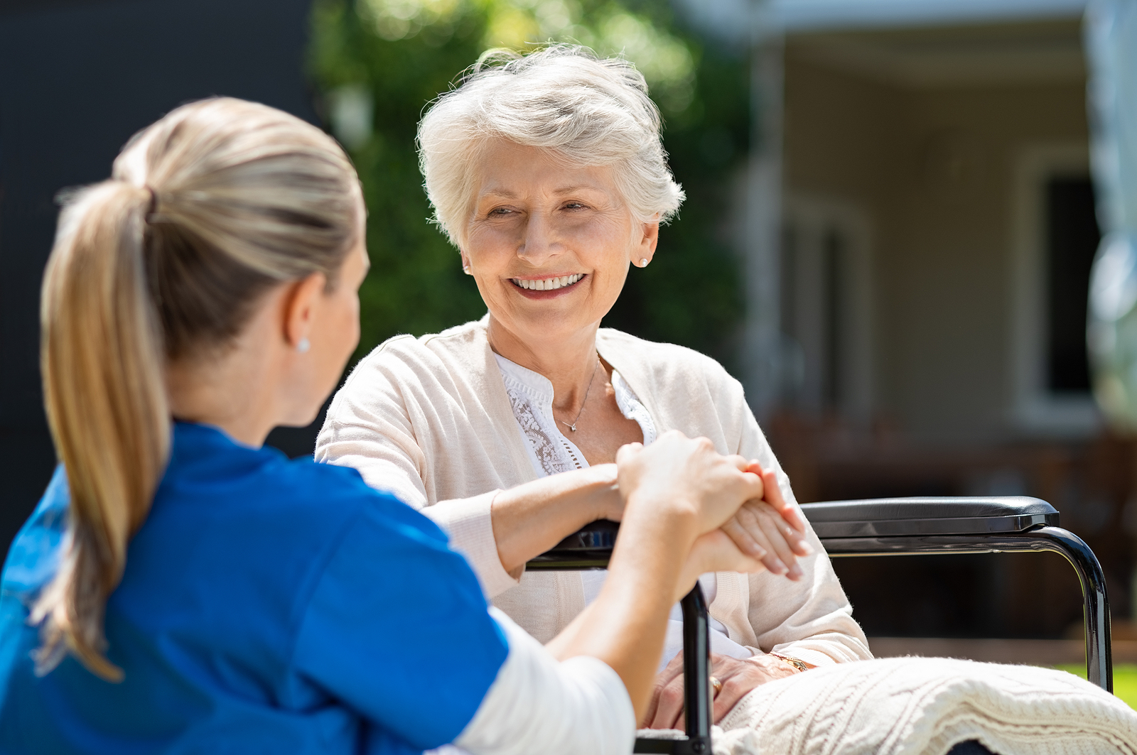 Senior woman smiles with a caregiver in a memory care community