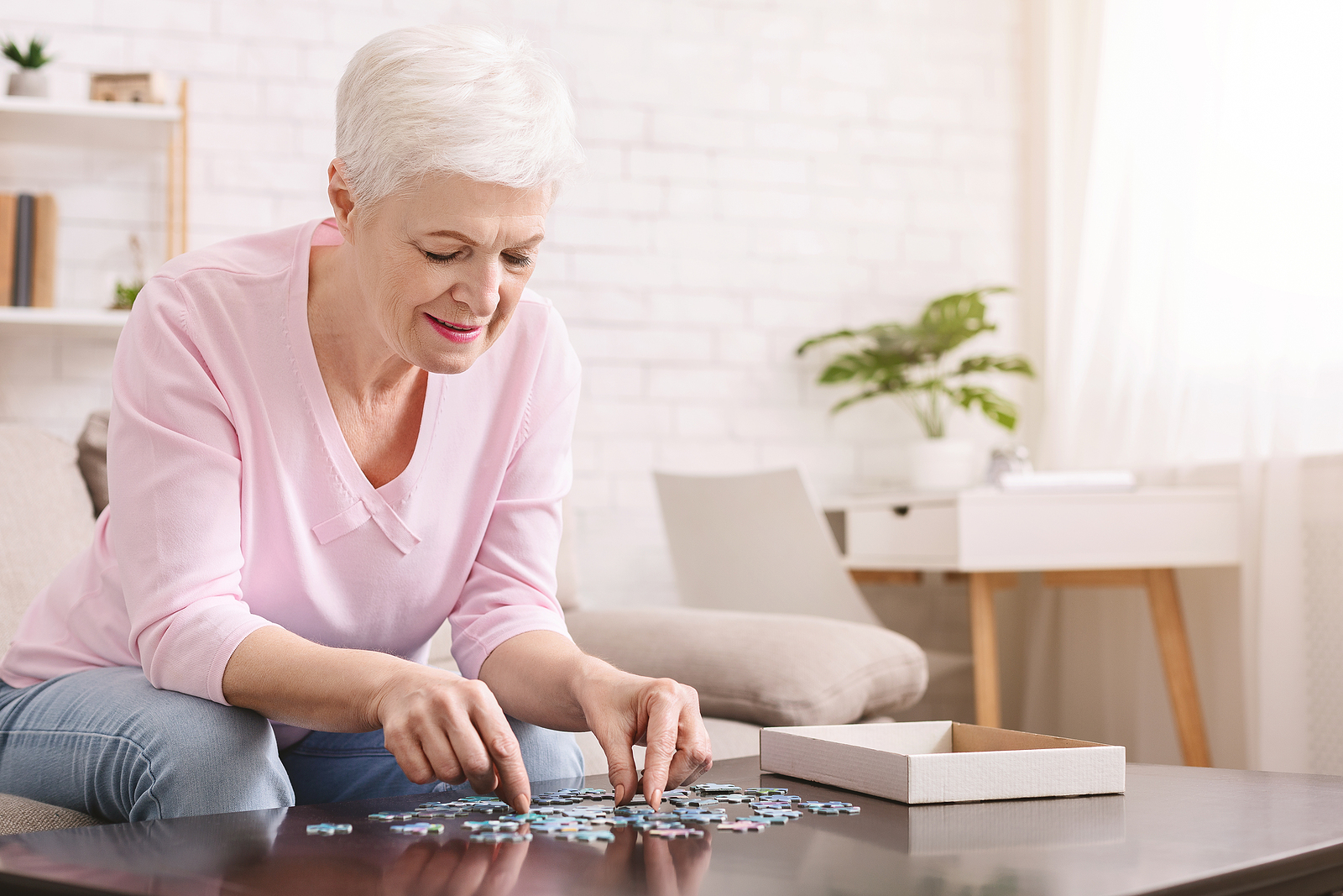 Senior woman works on a puzzle in a memory care community