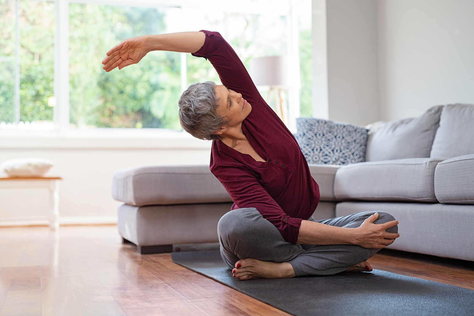 An older woman stretching and exercising from the comfort of her own home