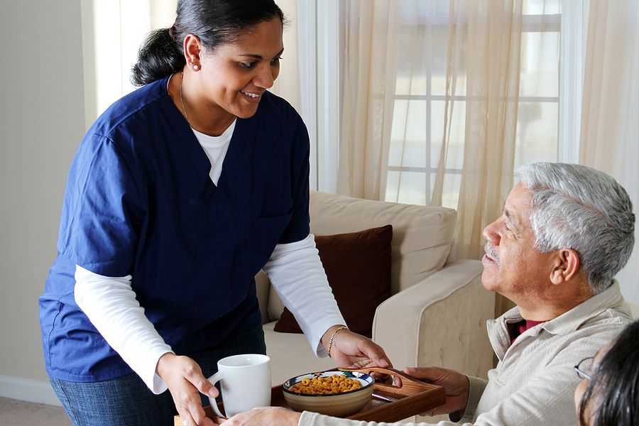 Caregiver providing happy senior with a meal at home