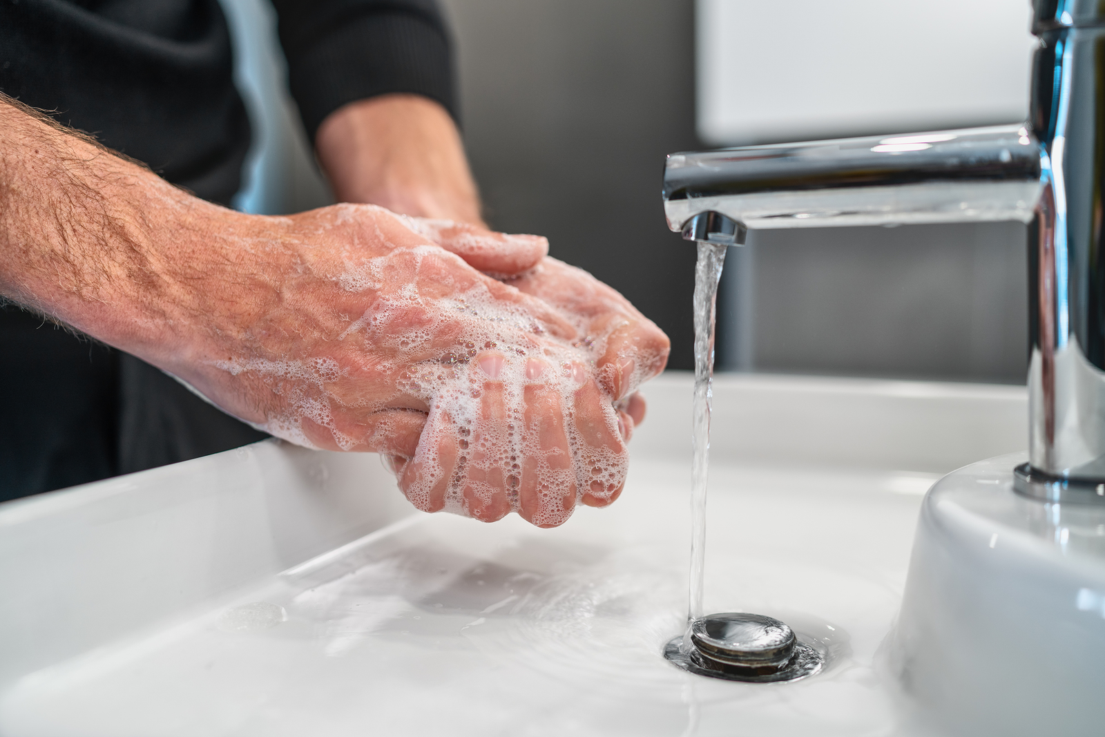 An older man washing his hands to help prevent the spread of germs