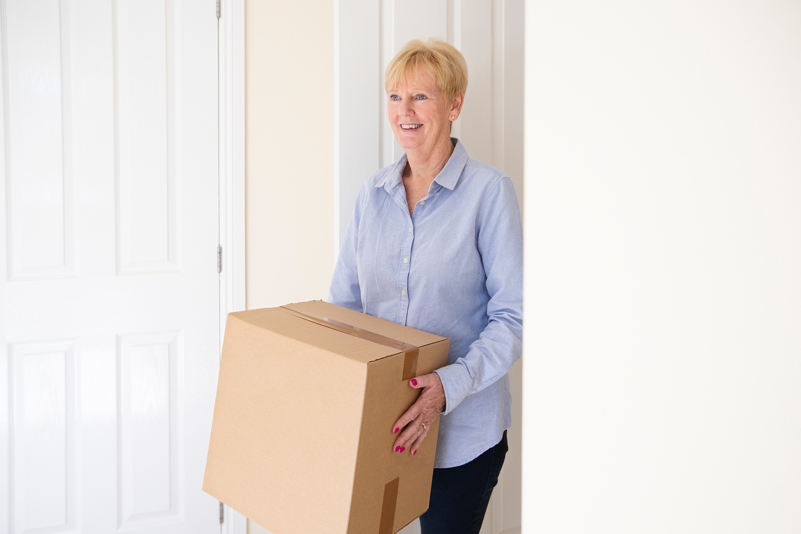 Senior woman carrying boxes into her new home after downsizing