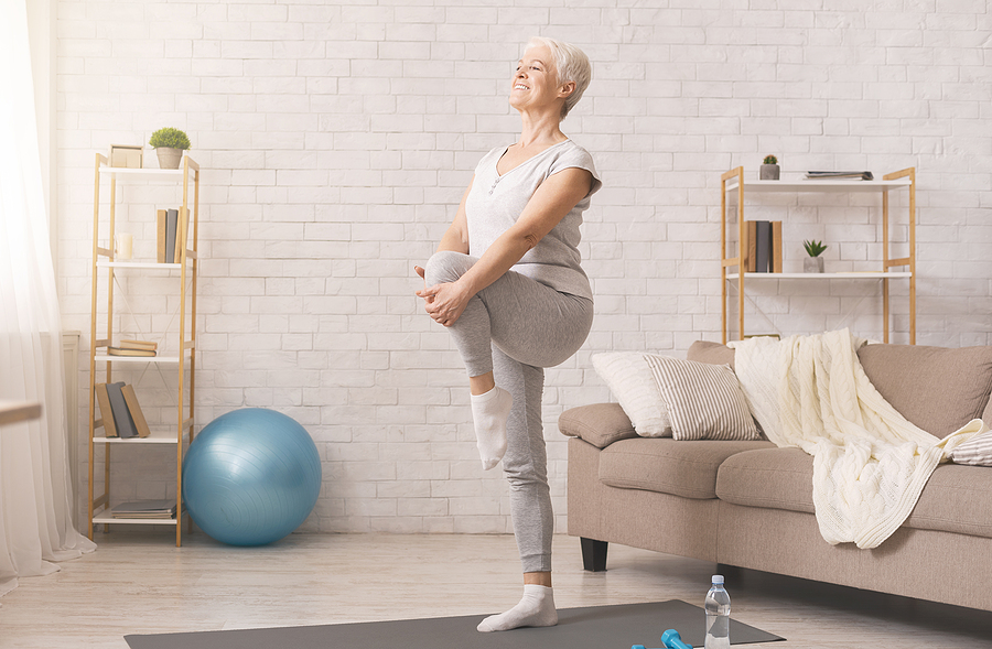 Happy senior woman practices a balance exercise in her living room