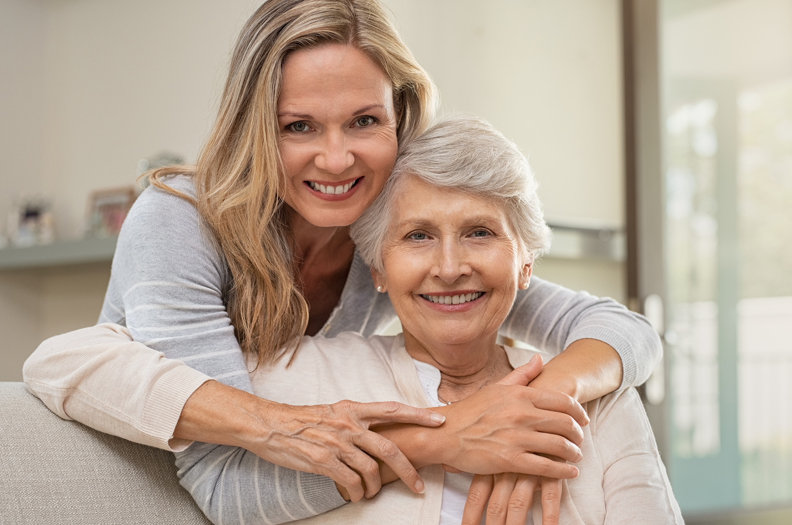 Portrait of elderly mother and middle aged daughter smiling together