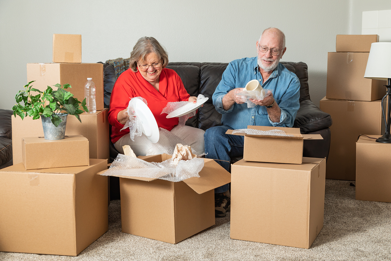 Happy senior couple packs their belongings into boxes preparing to move