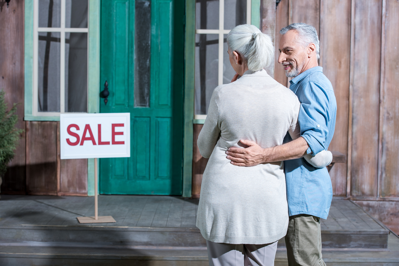 Smiling senior couple selling their house
