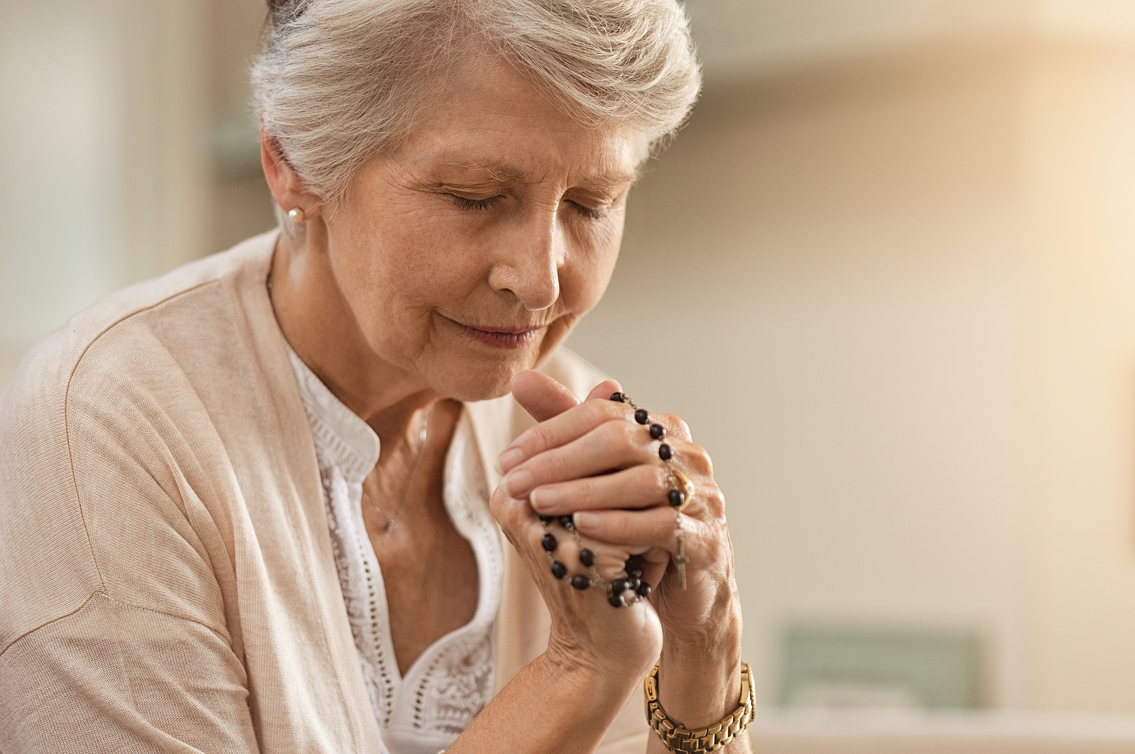 A senior woman practices her spiritual wellness by praying with a rosary