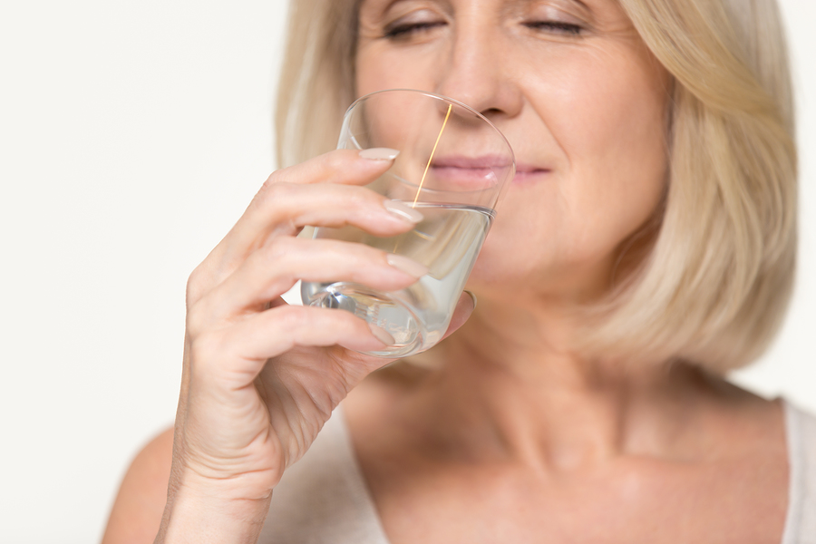 A senior woman drinks water to stay hydrated