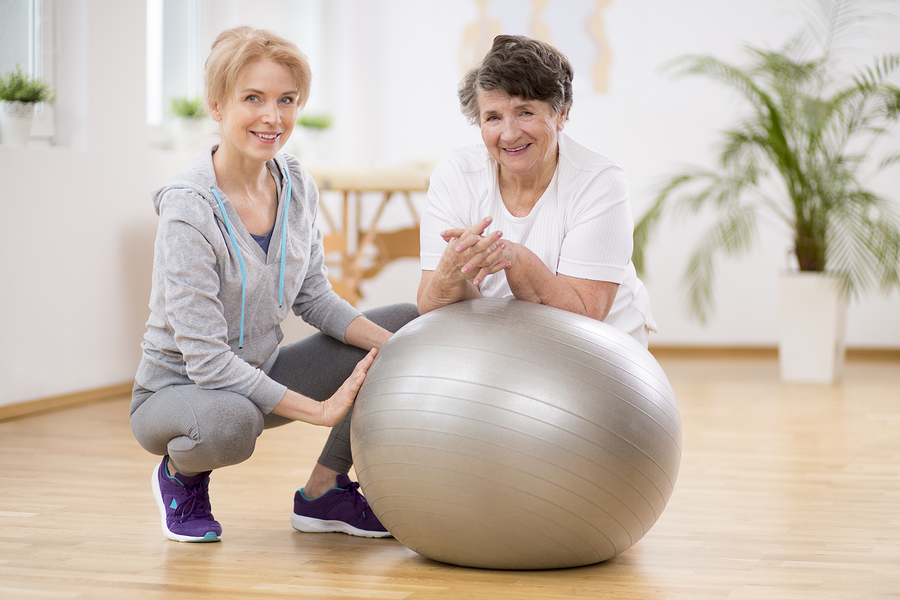 A senior woman uses an exercise ball during physical therapy at home