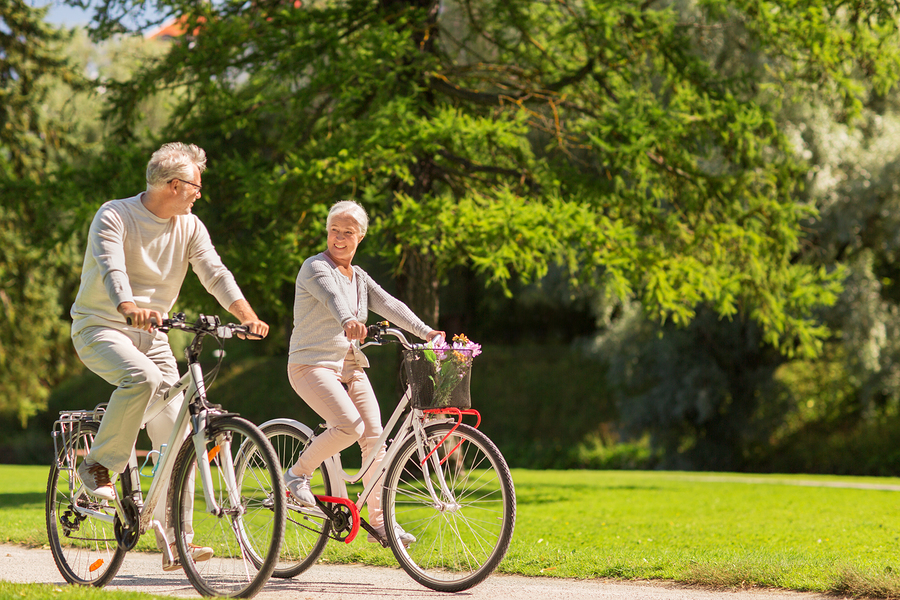 A senior couple riding their bikes together on a clear sunny day