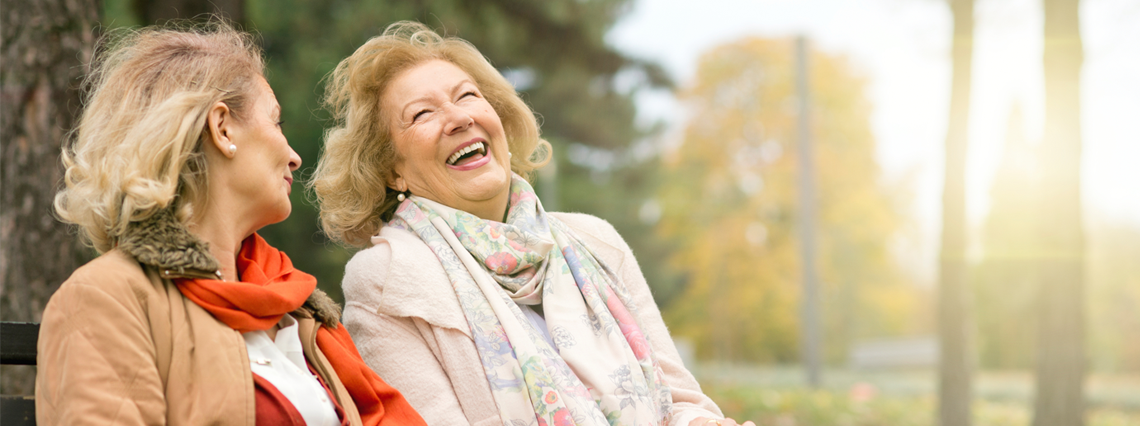 two senior women laughing in the park