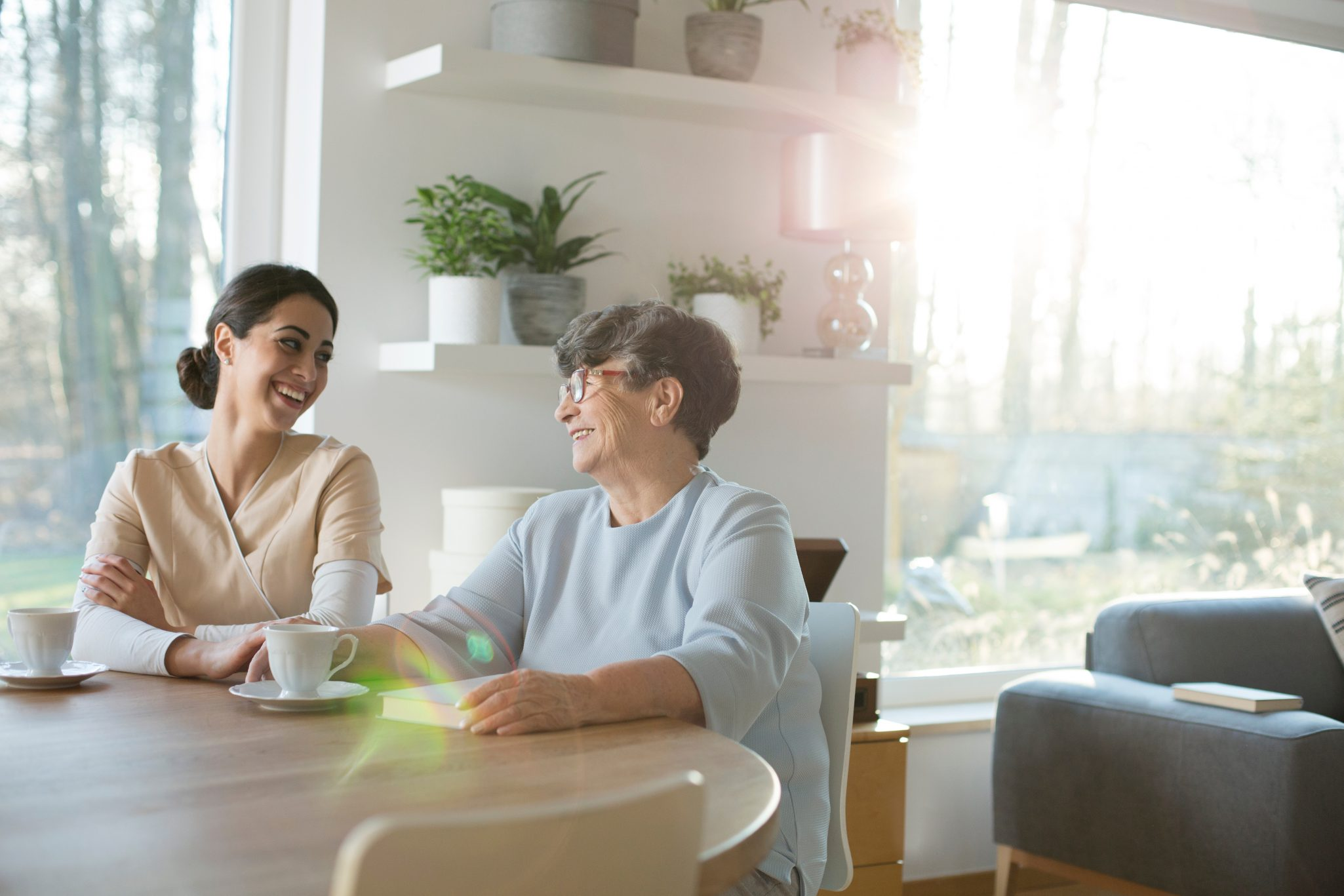 A senior woman sits at home at the coffee table with a speech therapist