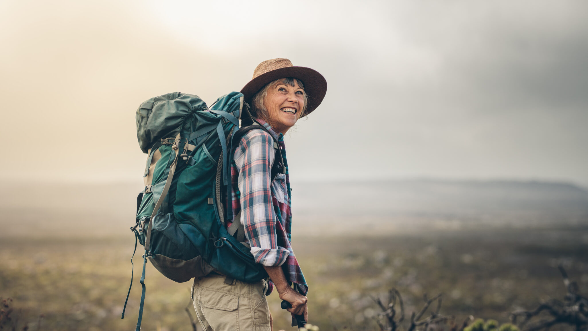 Senior walking on trail with hiking backpack on