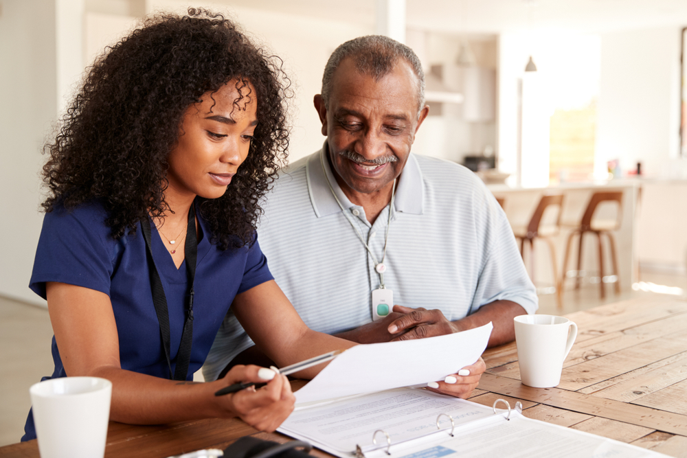 An in home care healthcare worker talks with a senior about his health tests