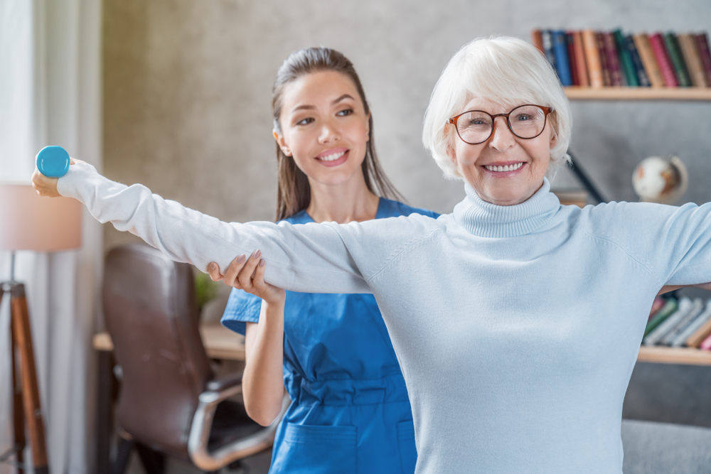 A physical therapists visits a senior woman at home to practice rehabilitation exercises