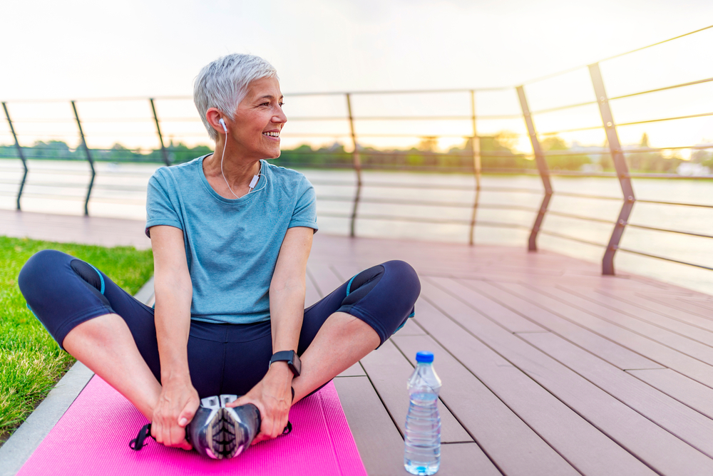 A senior woman sits on a yoga mat and does running stretches