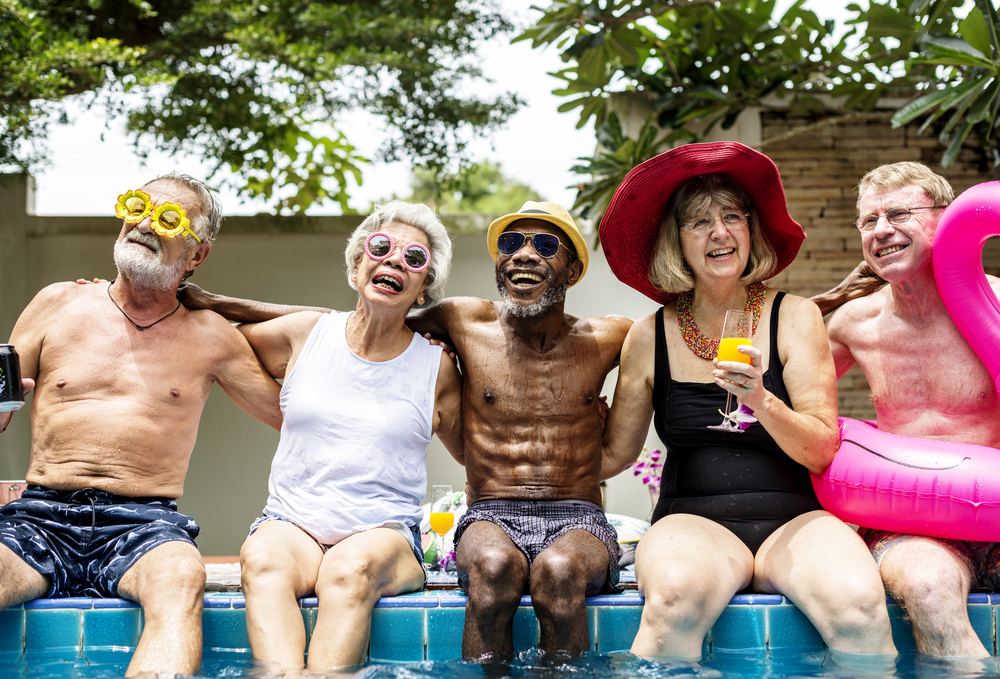 A group of seniors sitting at the pool laughing and having fun